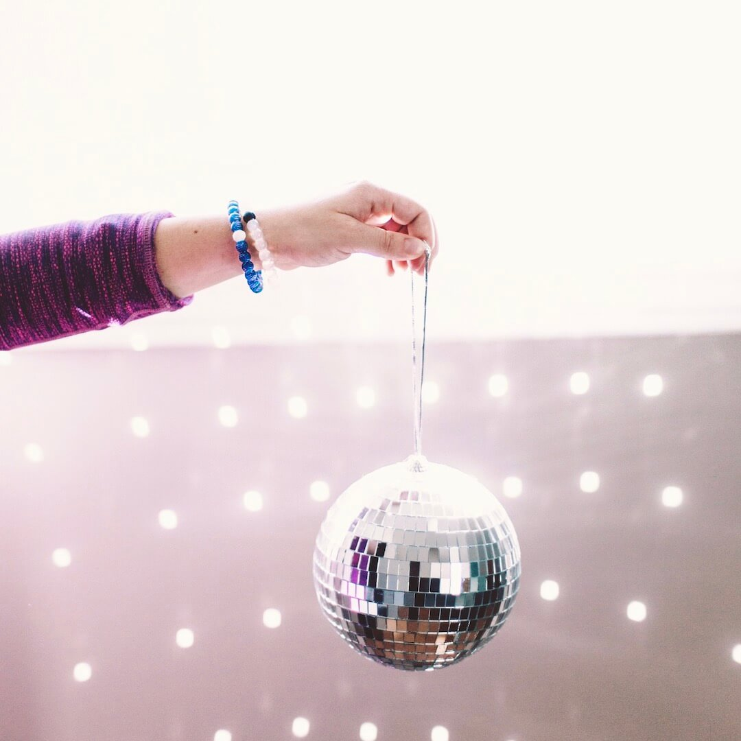 Person holding a disco ball with a silicone beaded bracelet with Virgo symbol pattern on wrist.