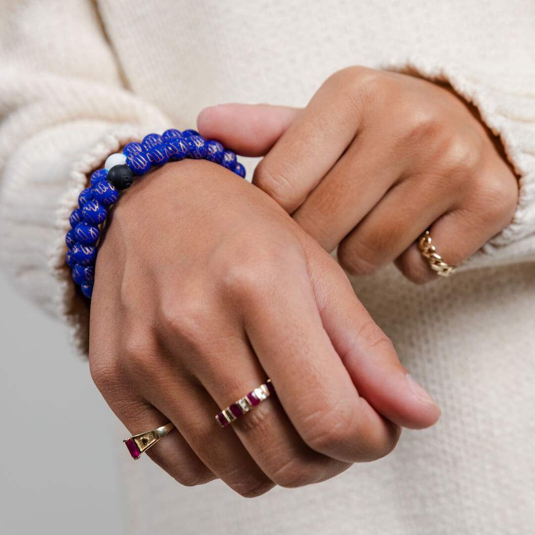 Girl wearing a silicone beaded bracelet with Virgo symbol pattern on wrist.