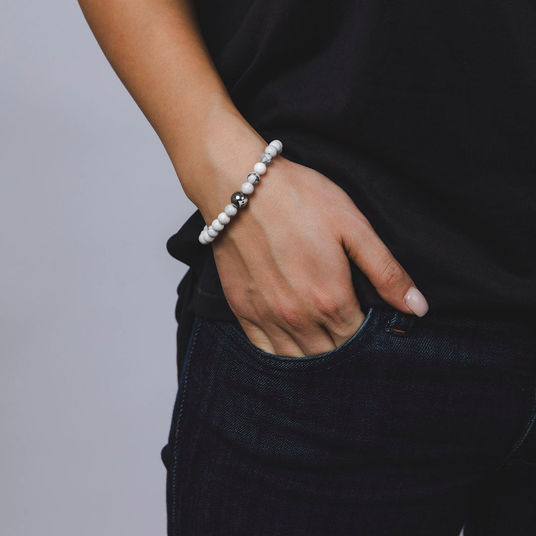 Female wearing white turquoise stone bracelet on wrist with hand in pocket.