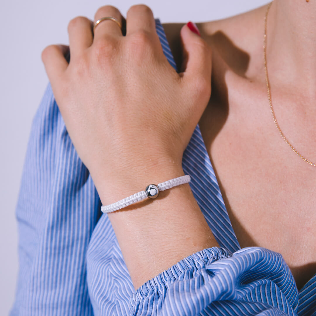 Female wearing white woven bracelet with silver metal bead with her arm resting on her shoulder.