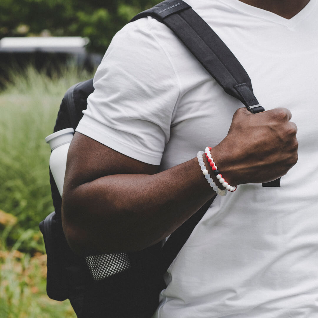 Man holding backpack strap wearing a white and red silicone beaded bracelet.