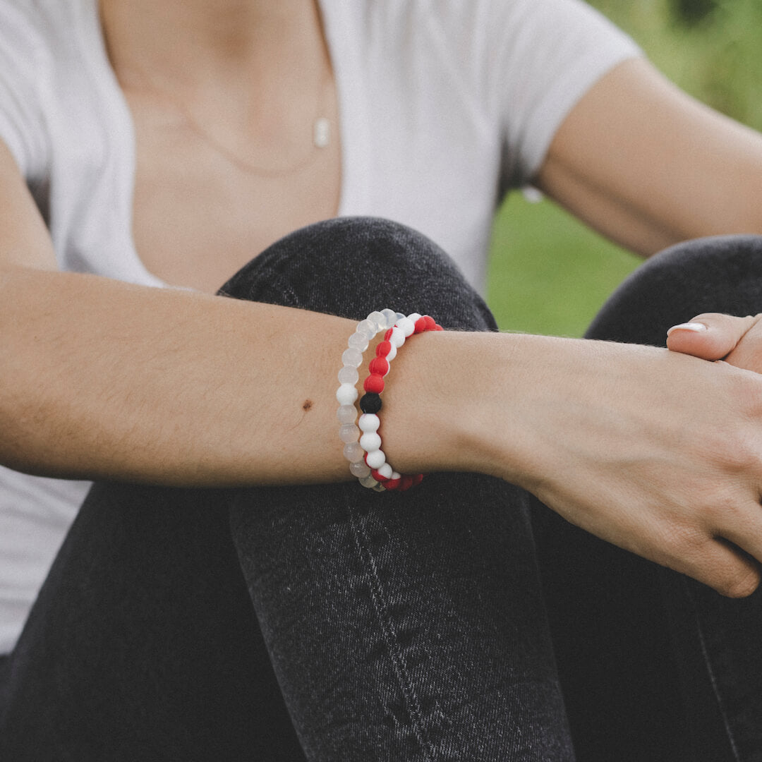 Close-up of a woman wearing a white and red silicone beaded bracelet.