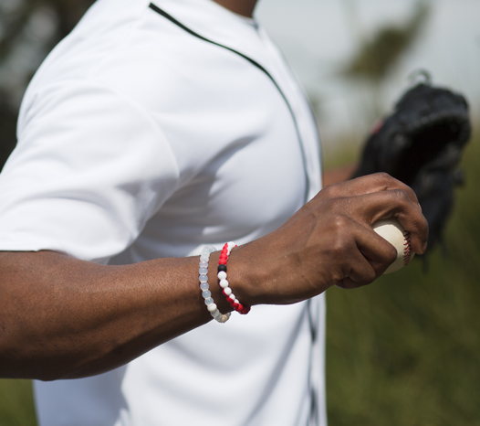 Male with red and white swirl silicone beaded bracelet on wrist while holding a baseball.