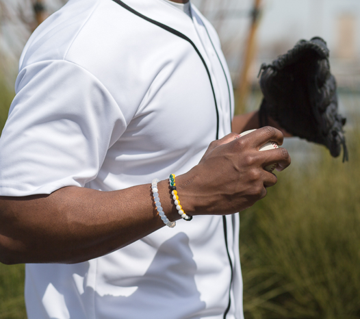 Male wearing yellow, green and white silicone beaded bracelet on wrist while holding a baseball.