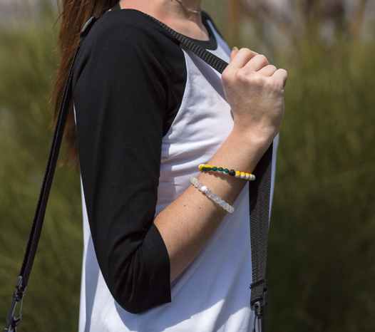 Woman wearing yellow, green and white silicone beaded bracelet on wrist while holding shoulder bag strap.