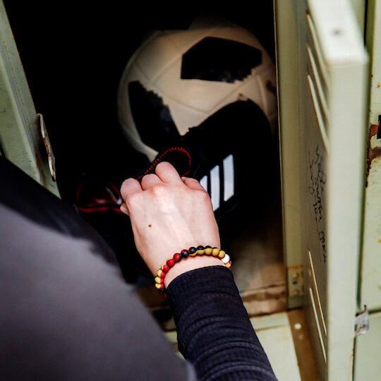 A hand wearing a red, black, and gold swirl silicone beaded bracelet in a locker