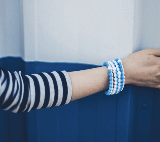 Person wearing stack of half light blue half white silicone beaded bracelets on wrist while touching blue and white wall.