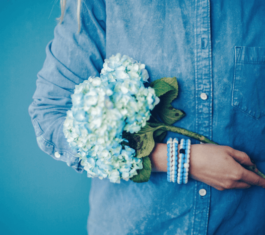Woman wearing stack of half light blue half white silicone beaded bracelets on wrist while holding blue flowers.