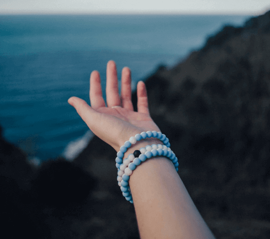 Close up of hand with half light blue half white silicone beaded bracelets on wrist with ocean in the background.