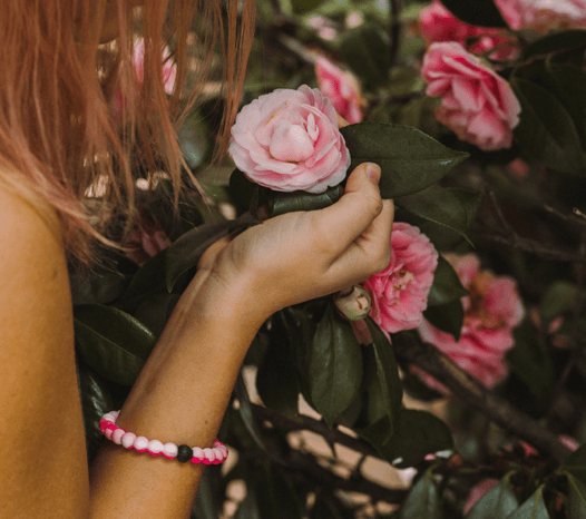 Woman wearing pink swirl silicone beaded bracelet while holding pink flowers.