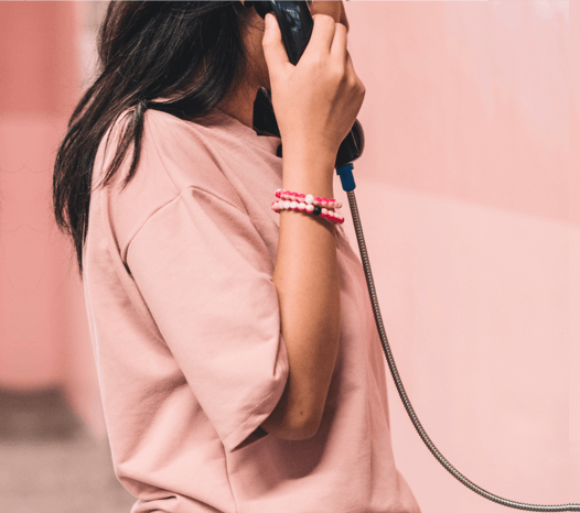 Woman wearing two pink swirl silicone beaded bracelets on wrist while holding a phone.