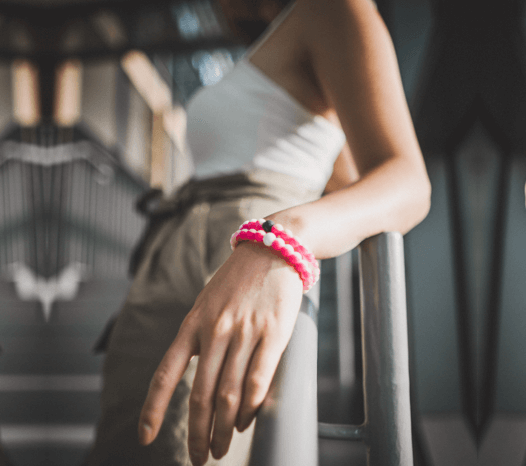 Woman leaning on handrail with a close up of pink swirl silicone beaded bracelets on her wrist.
