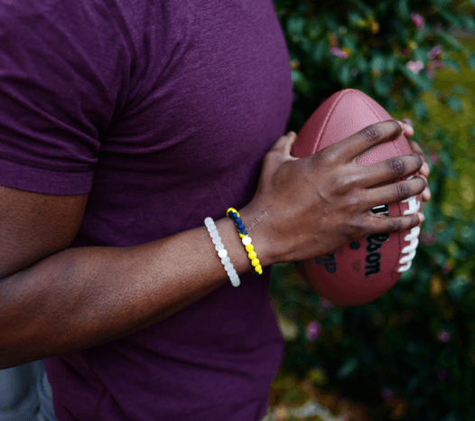 Man holding a football wearing a yellow and navy blue silicone beaded bracelet.