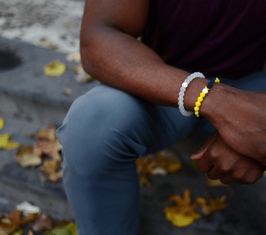 Man holding his wrist wearing a yellow and navy blue silicone beaded bracelet.