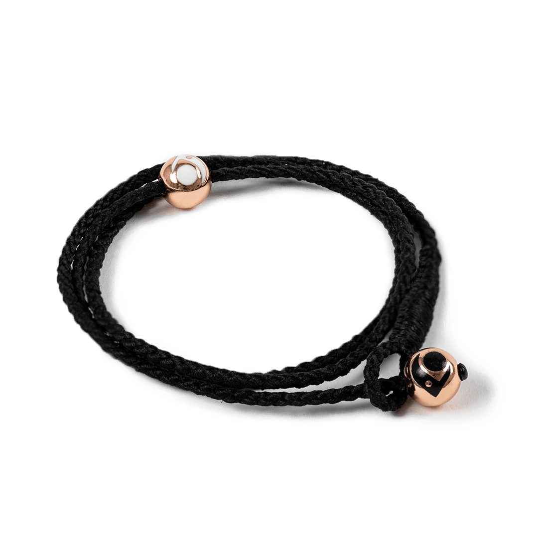 Side angle of black triple wrap woven bracelet with two rose gold metal beads.