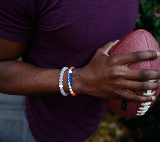 Man holding football wearing an orange, grey and blue silicone beaded bracelet.