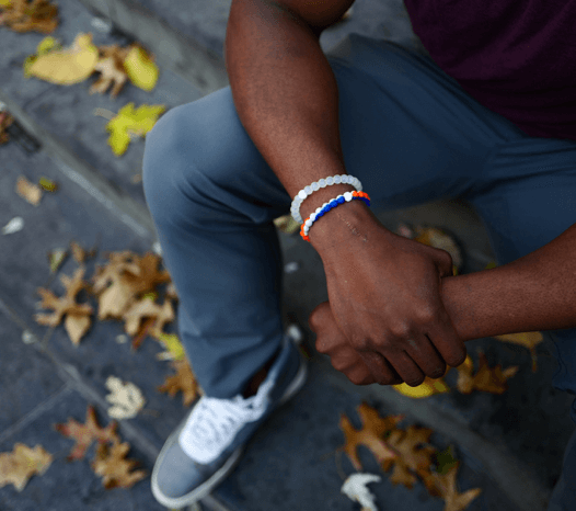 Man sitting on steps wearing an orange, grey and blue silicone beaded bracelet.