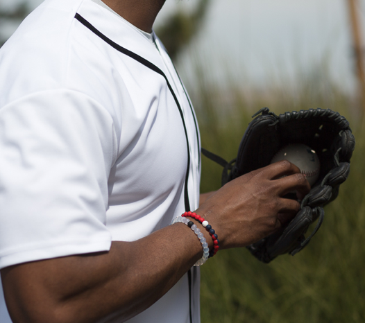 Male wearing red and navy blue silicone beaded bracelet on wrist while holding a baseball.