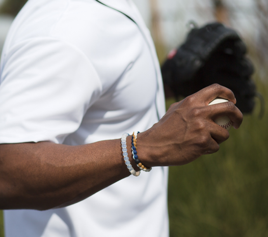 Male wearing blue, white and tan silicone beaded bracelet on wrist while holding a baseball.
