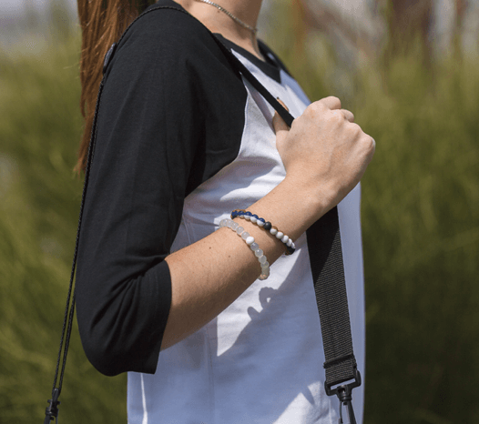 Woman wearing blue, white and tan silicone beaded bracelet on wrist while holding shoulder bag straps.