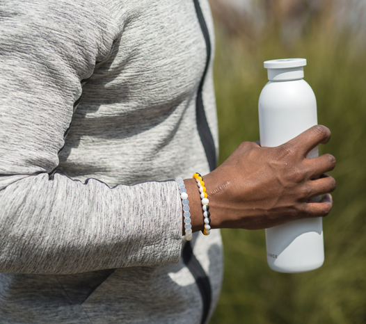 Male wearing a black, gold and white silicone beaded bracelet on wrist while holding a water bottle.