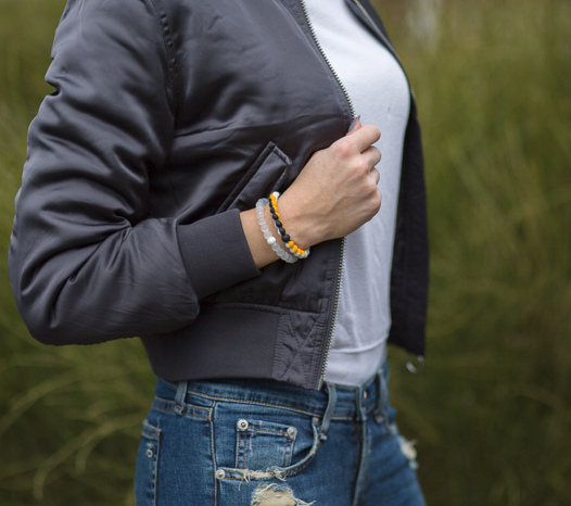 Woman wearing a gray bomber jacket with a black, gold and white silicone beaded bracelet on wrist.