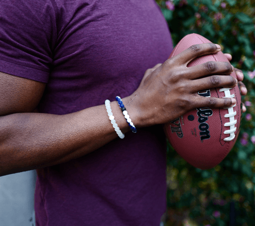 Man holding a football wearing a navy blue and white silicone beaded bracelet.
