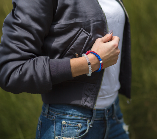 Woman wearing a gray bomber jacket with a burgundy and blue silicone beaded bracelet on wrist.