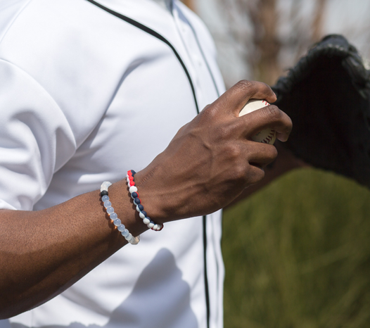 Male wearing red, white and navy blue silicone beaded bracelet on wrist while holding a baseball.