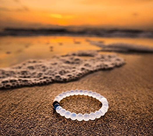Clear silicone beaded bracelet on beach with waves and a sunset in the background.