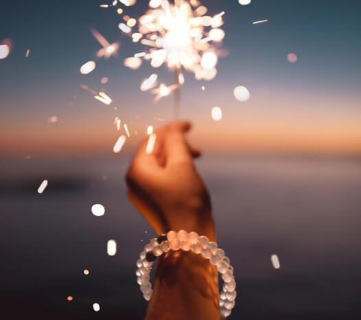 Hand holding sparklers with a clear silicone beaded bracelet on wrist.