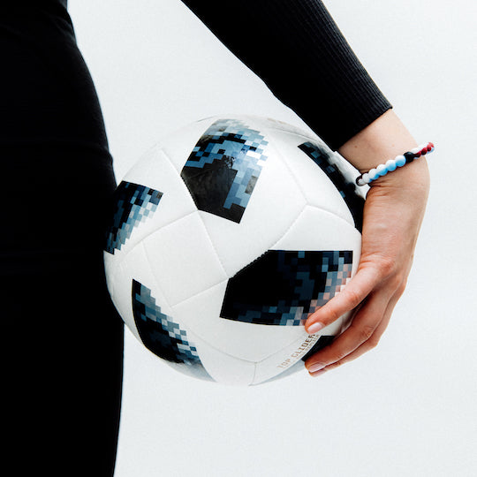 A hand holding a soccer ball wearing a maroon, white, and light blue swirl silicone beaded bracelet.