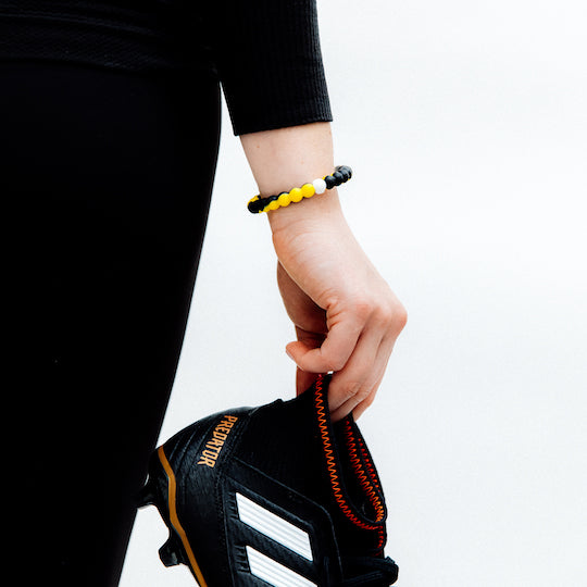 A hand holding soccer cleats wearing a black and yellow swirl silicone beaded bracelet