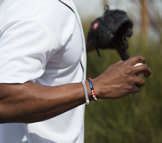Male wearing blue, white and red silicone beaded bracelet on wrist while holding a baseball.