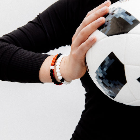 A close-up of a hand holding a soccer ball wearing a black and red swirl silicone beaded bracelet