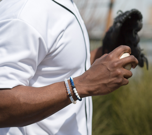 Male wearing navy blue and white silicone beaded bracelet on wrist while holding a baseball.