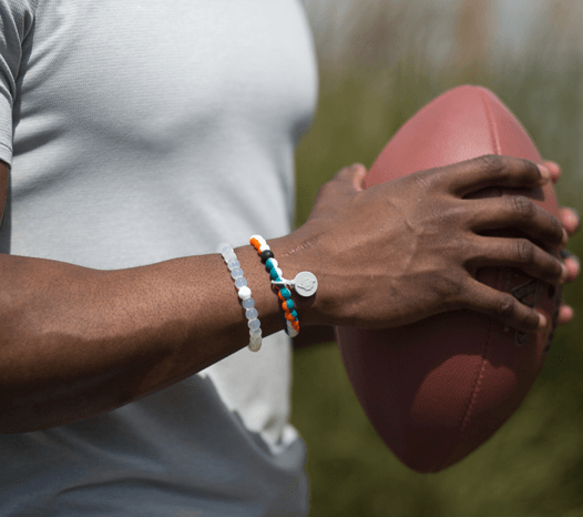 Male wearing an aqua, orange and navy blue silicone beaded bracelet on wrist while holding a football.