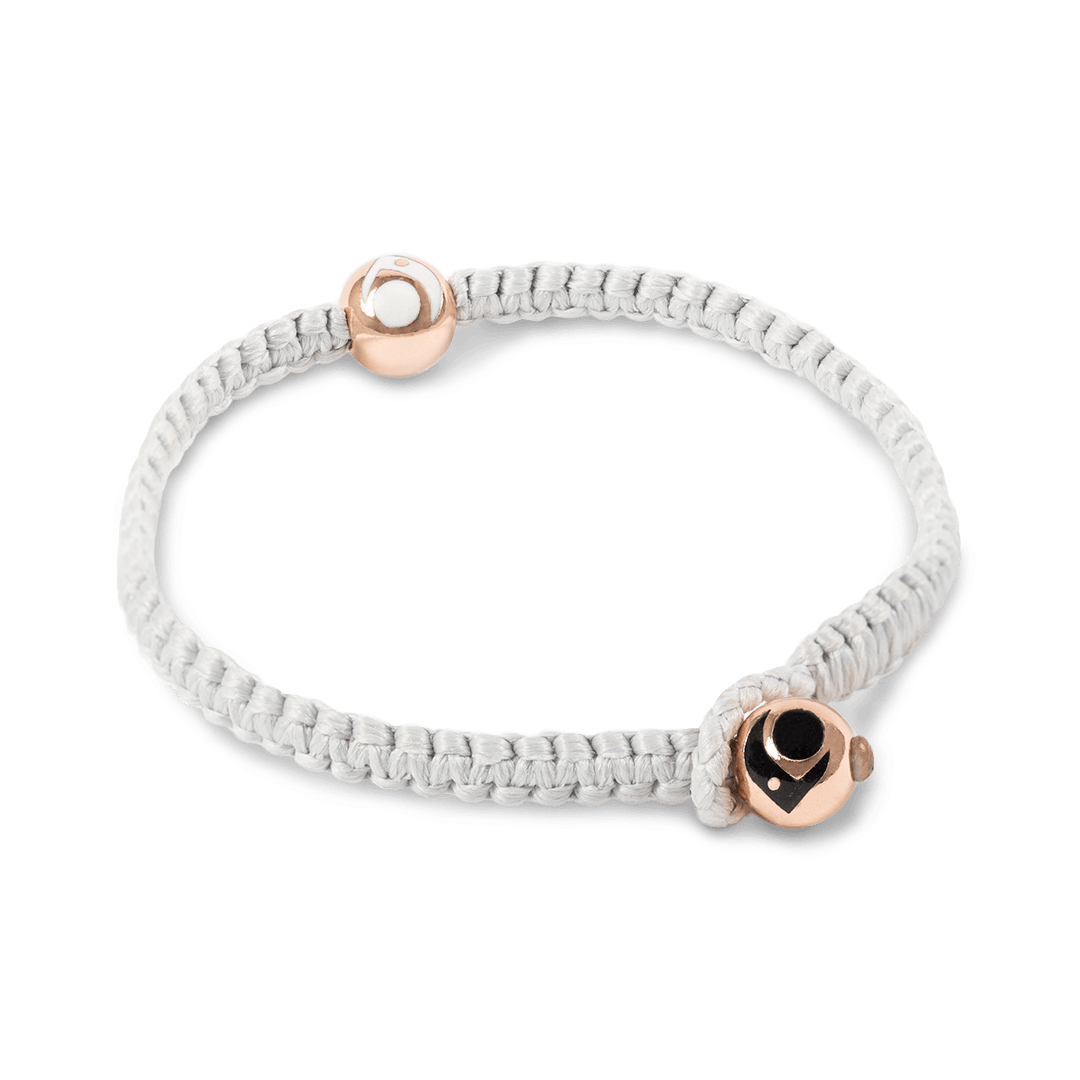 Side angle of light gray woven bracelet with two rose gold metal beads.