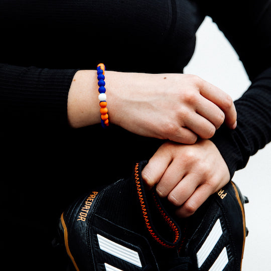 A hand wearing an orange and blue swirl silicone beaded bracelet resting on another hand holding soccer cleats