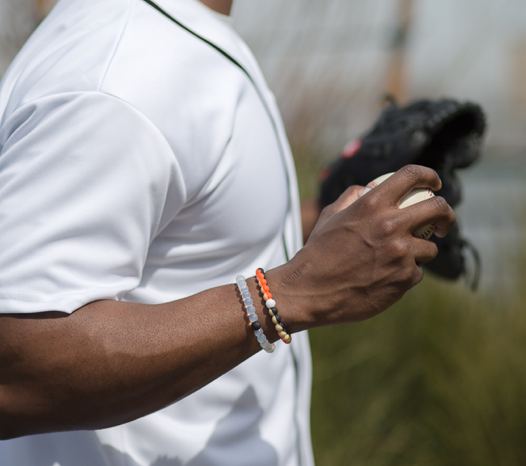 Male wearing orange, black and tan silicone beaded bracelet on wrist while holding a baseball.