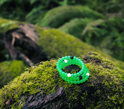 Stack of green silicone beaded bracelets on rock with moss.