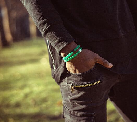 Male wearing all black with two green silicone beaded bracelets on wrist with his hand in his pocket.