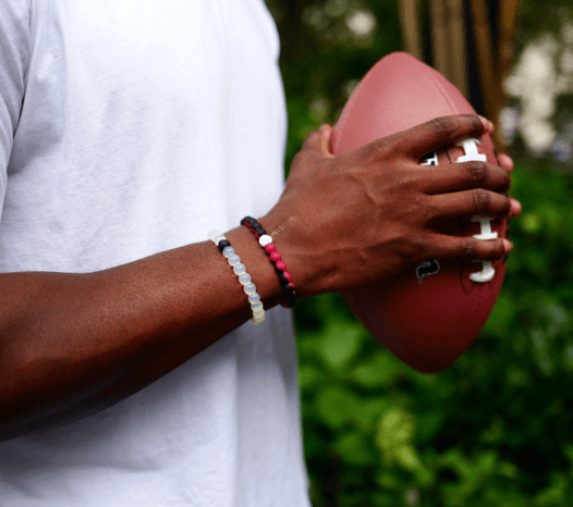 Man holding a football wearing a red and black silicone beaded bracelet.