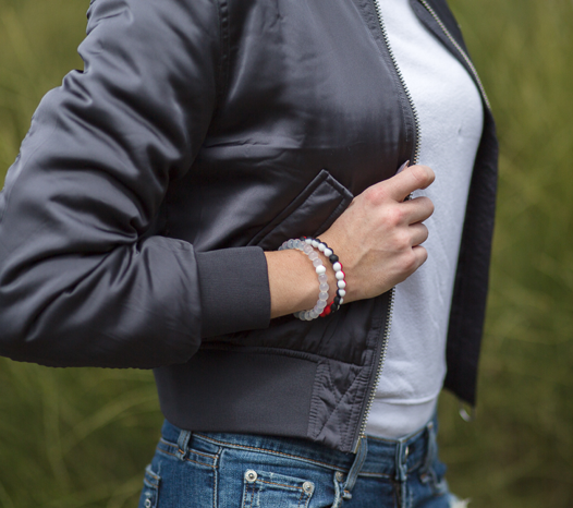 Woman wearing a gray bomber jacket with a red, black and white silicone beaded bracelet on wrist.