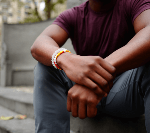Man holding his wrist wearing a red, yellow and white silicone beaded bracelet.