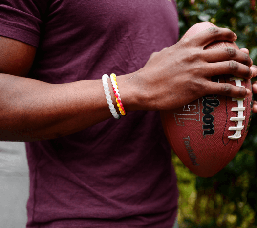 Man holding a football wearing a red, yellow and white silicone beaded bracelet.