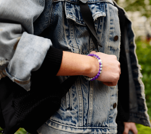 Close-up of a woman holding backpack strap wearing a gray and purple silicone beaded bracelet.