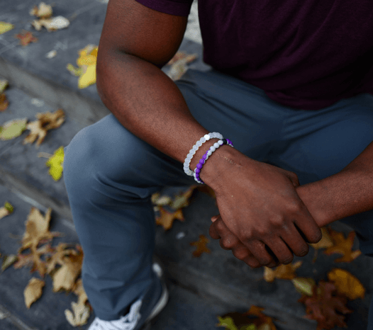 Man holding his hands wearing a gray and purple silicone beaded bracelet.