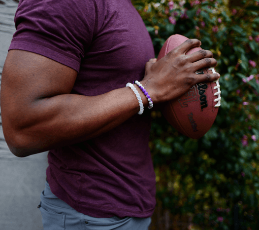 Man holding a football wearing a gray and purple silicone beaded bracelet.