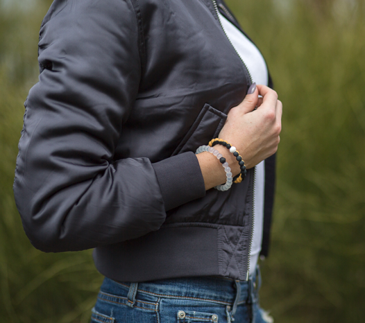 Woman wearing a gray bomber jacket with a black, gold and orange silicone beaded bracelet on wrist.